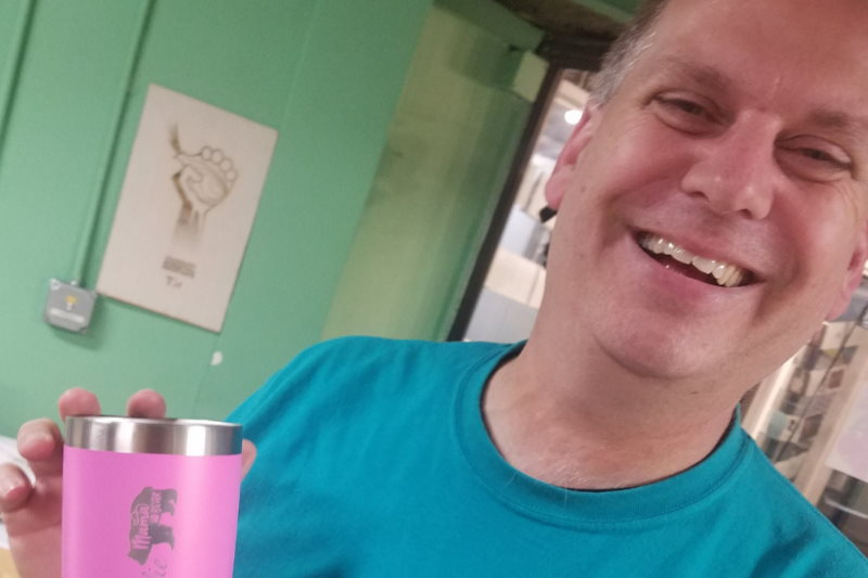 Happy AHA member with laser engraved coffee travel mug